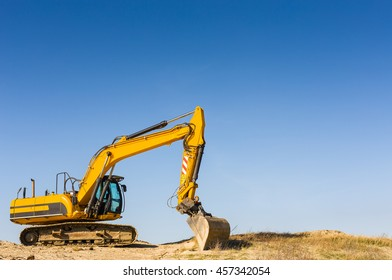 Heavy yellow excavator on the beach under a clear blue sky. Brand names removed.
