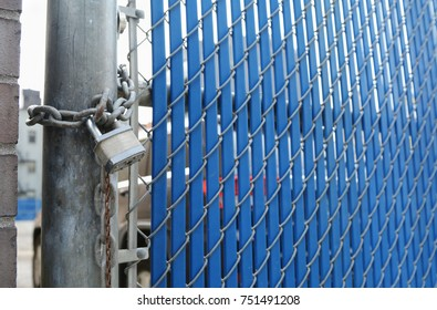 Heavy-duty padlock and chain locking security gate made of metal chainlink and blue plastic