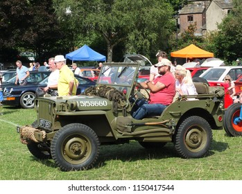 Hebden Bridge, West Yorkshire, England - August 4 2018: A group of people sat in a vintage military jeep and others looking at vintage cars at hebden bridge vintage weekend public vehicle show
