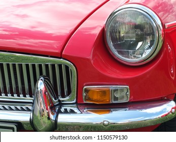 Hebden Bridge, West Yorkshire, England - August 5 2018: front close up of a red british mgb sports car showing headlamp and chrome bumper at the Annual Hebden Bridge Vintage Weekend Vehicle Show