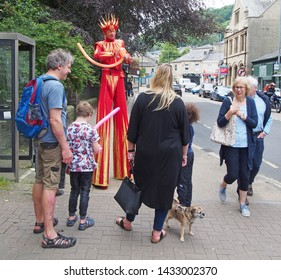 hebden bridge, west yorkshire, united kingdom - 23 june 2019: a man in a bright costume on stilts making balloon animals for a family in the street at hebden bridge public arts festival