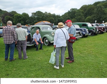 hebden bridge, west yorkshire, united kingdom - 4 august 2019: older people talking around lines of cars in the public park at hebden bridge annual vintage weekend