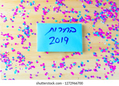 Hebrew text Elections 2019 on voting paper over wooden board with confetti background. Israeli legislative Elections for the 21st Knesset Israel 9 April 2019.