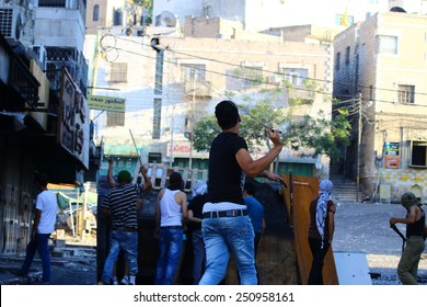HEBRON, PALESTINE - AUGUST 16, 2014: A Palestinian teenager winds up to hurl a stone at Israeli soldiers during clashes with protesters in Hebron, Palestine on August 16, 2014.
