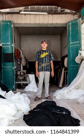 Hebron, Palestine, August 3, 2014: Palestinian young adult stand in a door of a sawing workshop.