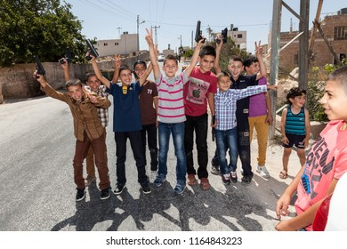 Hebron, Palestine, July 30, 2014: Palestinian children pose to the picture with fake guns in their hands on the streets of Hebron