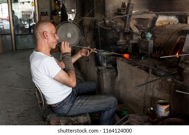 Hebron, Palestine, June 4, 2014: A Palestinian works by a stove in a Phoenician glass workshop which produces domestic decoration and utensils.