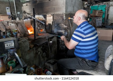 Hebron, Palestine, June 4, 2014: A Palestinian lights a cigarette while working in very harsh conditions in a Phoenician glass workshop which produces domestic decoration and utensils.