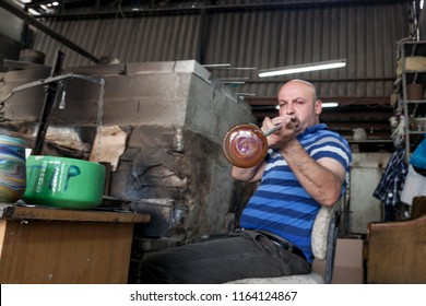 Hebron, Palestine, June 4, 2014: A Palestinian blows a glass vase in a Phoenician glass workshop which produces domestic decoration and utensils.