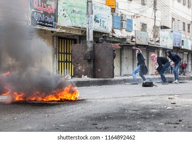Hebron, Palestine, November 29, 2013:   Young Palestinians are hiding behind a board and a smoke of burning tire during riots in Hebron's old town.