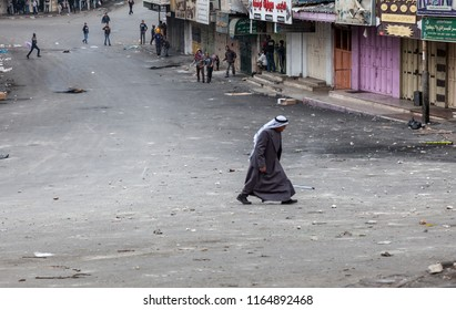 Hebron, Palestine, November 29, 2013: Palestinian elderly is walking across a street what stops the youth throwing stones at Israeli soldiers during riots in Hebron's old town.