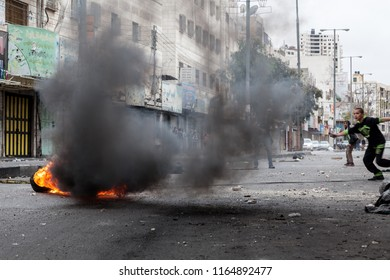 Hebron, Palestine, November 29, 2013:   Young Palestinians are hiding behind the smoke of burning tire during riots in Hebron's old town.