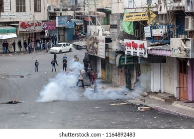 Hebron, Palestine, November 29, 2013: Young Palestinians are standing on the streets amid tear gas during riots in Hebron's old town.