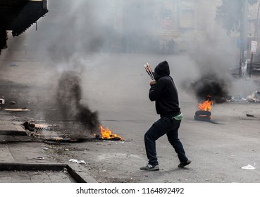 Hebron, Palestine, November 29, 2013:  Young Palestinians is shooting a stone from a sling towards Israeli soldiers during riots in Hebron's old town.