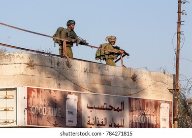 Hebron, Palestine, November 7 2010: Israeli soldiers patrol streets of old town Hebron. Hebron old town has been closed by Israel Defence Forces to protect group of Jew who  illegally occupy the area