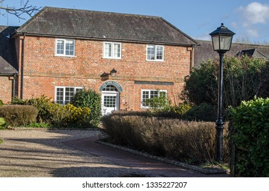 HECKFIELD, UK - MARCH 10, 2019: Residential accommodation in the historic village of Heckfield in Hampshire viewed from the street on a sunny winter afternoon.