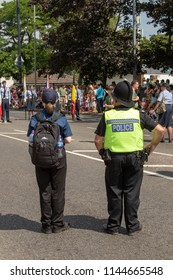 Hedge End, Hampshire, UK - July 4th 2018: A policeman and cadet watch the village carnival.