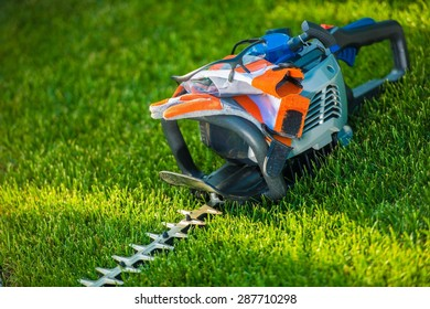 Hedge Trimming Safety. Powerful Gasoline Hedge Trimmer with Safety Accessories; Gloves and Safety Glasses. Landscaping Safety Concept.