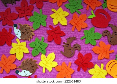 Hedgehog, squirrel and leaves out of felt on a pink fabric as a background