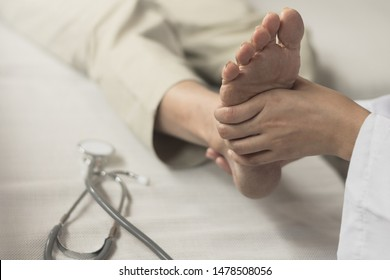 Heel Pain or plantar fasciitis concept. Doctor checking patient foot as suffer from inflammation feet problem of Sever's Disease or calcaneal apophysitis.
