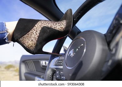 Heels and Cars - Luxurious Louboutin shoes and fast Mustang car in a dangerous combination - USA, January 2017