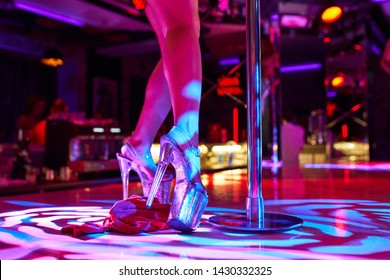 Heels of sexy woman pole dancing or striptease. Pylon in night club. Stripper girl background