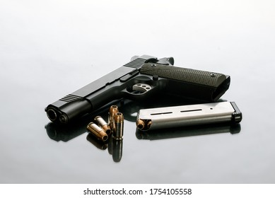 Hefty 1911 semi automatic handgun unloaded next to 8 round magazine and 4 loose hollow point bullets is a good choice for home protection from crimminals.