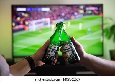 Heidelberg, Baden Württemberg / Germany - 05 26 2019: Toasting with Heineken Beer Close up Hands Capture at Football / Soccer Goal Celebration Time Defocused Flat TV Screen