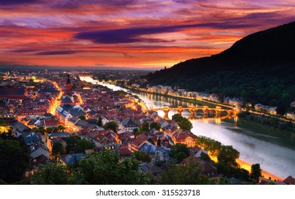 Heidelberg, Germany, aerial view at dusk, with dramatic sunset sky and the lights of the city, Neckar river and the Old Bridge
