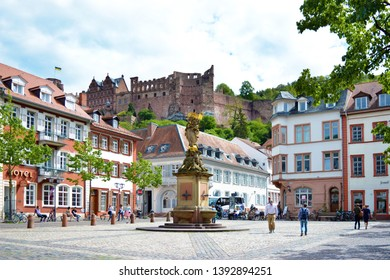 Heidelberg, Germany - April 2019: Square called 'Kornmarkt' in old city center with people walking by, fountain with golden Madonna statue and view on historical Heidelberg castle