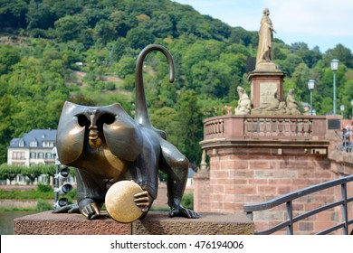 HEIDELBERG, GERMANY, AUGUST 23, 2015:  Bronze Statue of Monkey (Brueckenaffe) holding a mirror for wealth and showing sign of horns (Mano cornuta) at the old bridge (aka Karl Theodor) in HEIDELBERG