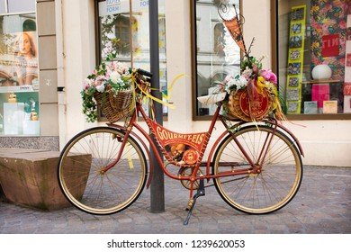 HEIDELBERG, GERMANY - AUGUST 25 : Classic retro vintage bicycle with flowers in basket stopping at front of store shop for people take photo at Heidelberger on August 25, 2017 in Heidelberg, Germany