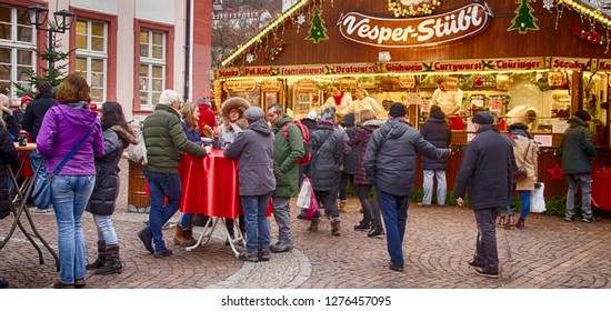 HEIDELBERG, GERMANY - DEC 19, 2018 - Visitors drink gluwein on a winter afternoon at the Christmas market,Heidelberg, Germany