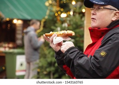 HEIDELBERG, GERMANY - DEC 19, 2018 - Visitors in early evening sample the food at   the Christmas market,Heidelberg, Germany
