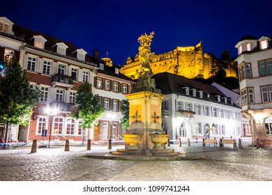 Heidelberg, Germany. The Madonna statue in Kornmarkt square at night, with Heidelberg Castle (Heidelberger Schloss) in the background