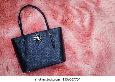 Heidelberg, Germany - November 11, 2019: GUESS women black leather handbag lying on a pink fur background. GUESS Open Road Tote Black bag 4G logo print. Open Road Logo Shopper