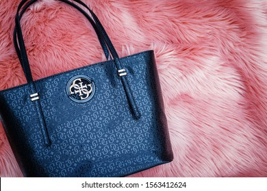Heidelberg, Germany - November 11, 2019: GUESS women black leather handbag on a pink fur background. GUESS Open Road Tote Black bag 4G logo print. Open Road Logo Shopper