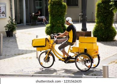 HEIDELBERG, GERMANY-AUGUST 25 : German people biking bicycle three wheels and cart send newspaper and brochure to house on road at Sandhausen district village on August 25, 2017 in Heidelberg, Germany
