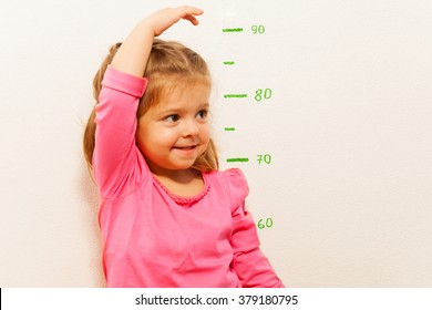 Height measurement by little girl at the wall