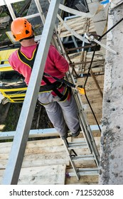 Height work on building and safety. Belaying the worker during work on a scaffolding.