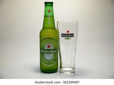 Heineken Beer Bottle And Branded Drinking Glass. Alcoholic Lager Beverage  Imported To US And Brewed