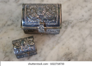 Heirloom, metal jewelry boxes on a marble  background