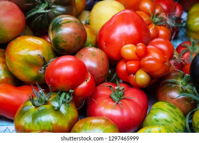 Heirloom organic imperfect tomatoes at local farmer market in France. Natural vegetable food background.
