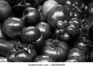 Heirloom organic imperfect tomatoes at local farmer market in France. Natural vegetable food background. Black and white photo.