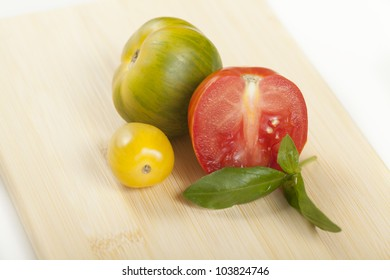 Heirloom tomatoes and basil on a cutting board.