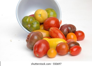 Heirloom tomatoes spilling out of a bowl on white seemless