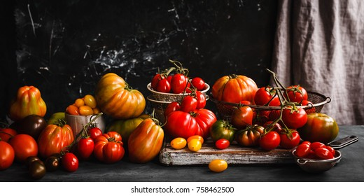 Heirloom variety tomatoes on dark rustic table text abundance ripe tomatoes