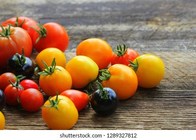 Heirloom variety tomatoes on rustic table. Colorful tomato - red,yellow , black, orange. Harvest vegetable cooking conception .