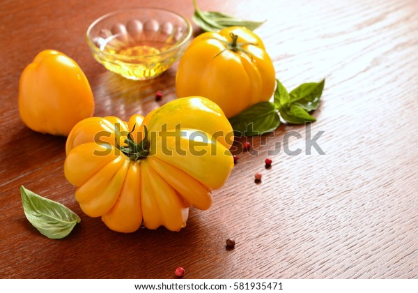 Heirlooms organic yellow tomatoes with basil and olive oil, copy space