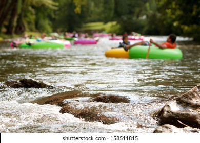 HELEN, GA - AUGUST 24:  De-focused people enjoy tubing down the Chattahoochee River in North Georgia on a summer afternoon, as boulders in foreground are in focus, on August 24, 2013 in Helen, GA.